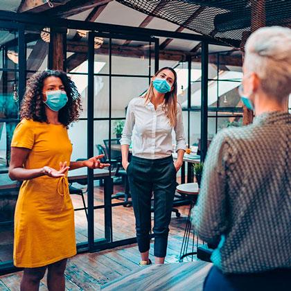 Vier Menschen mit Mund-Nasenschutz/ Four people wearing face coverings